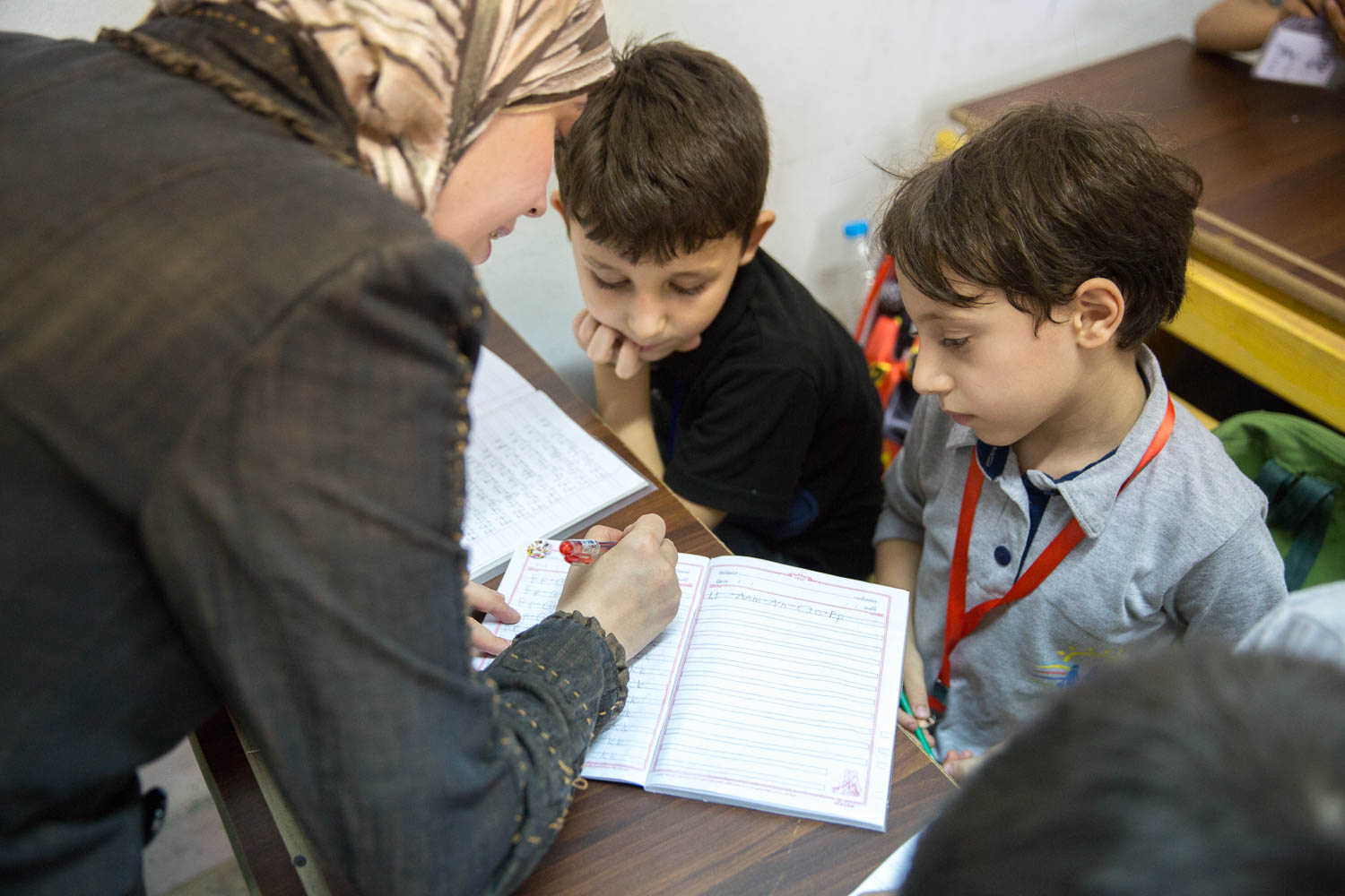 A teacher helps children write the alphabet during one of their first English lessons at the community centre run by NGO Ansan and Plan International. Most of the teachers at the community centre are Syrian refugees themselves.