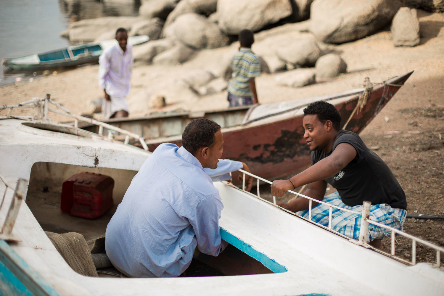 Young men repair the siding of a boat on the Nile river bank on Heisa Island.