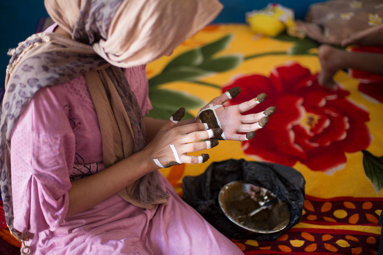 Noha applies henna to her hands in preparation for her engagement, on Seheil Island.