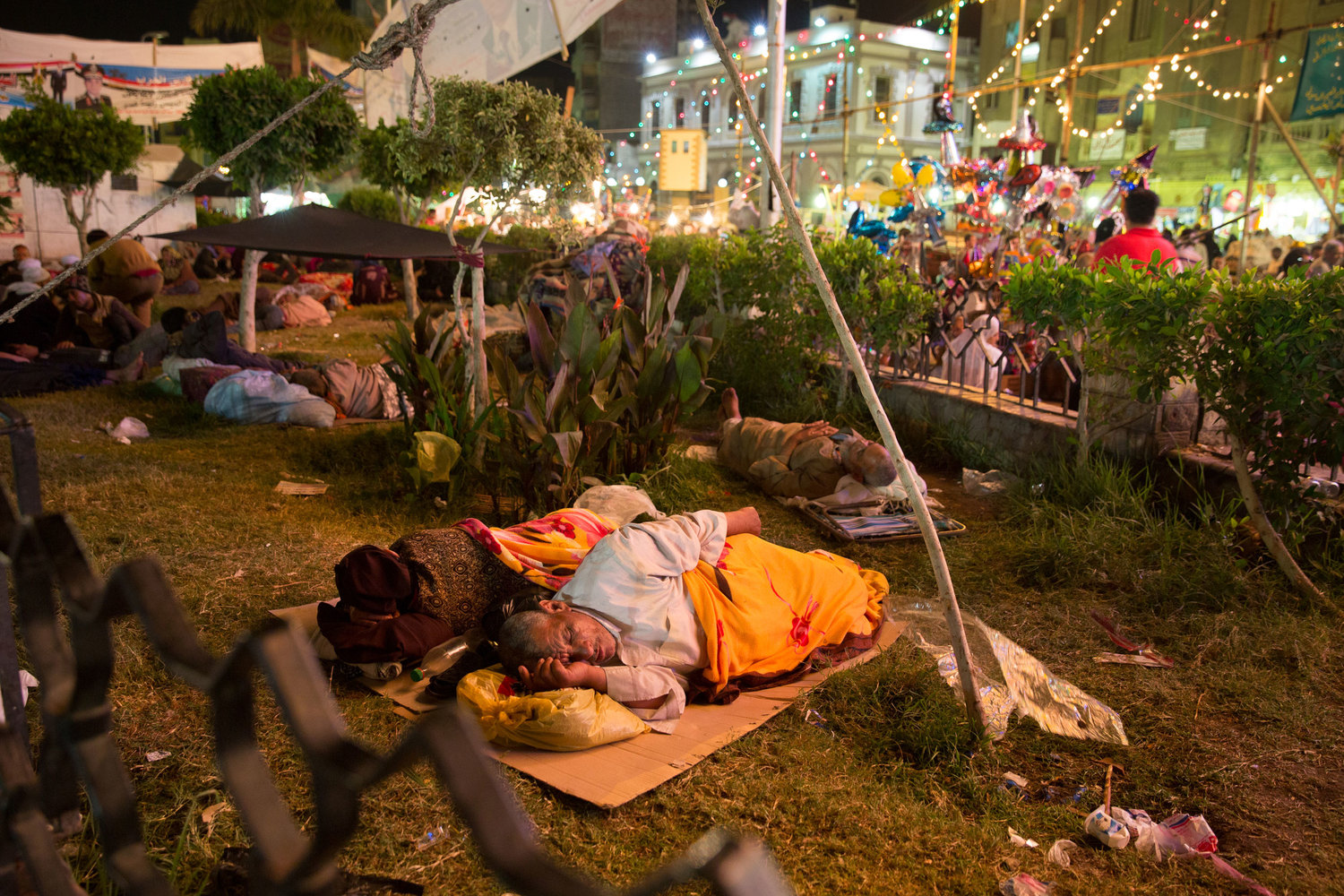 An elderly couple sleeps in a small park surrounded by the Sayeda Zeinab moulid festivities. The festival brings thousands of people from all over the country who often live and sleep in the neighborhood streets during the entire festival.